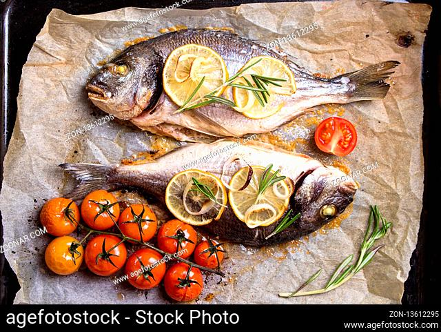 Tasty baked whole fish on baking paper. Baked sea bream with lemon, onion, herbs, cherry tomatoes, spices on dark rustic background