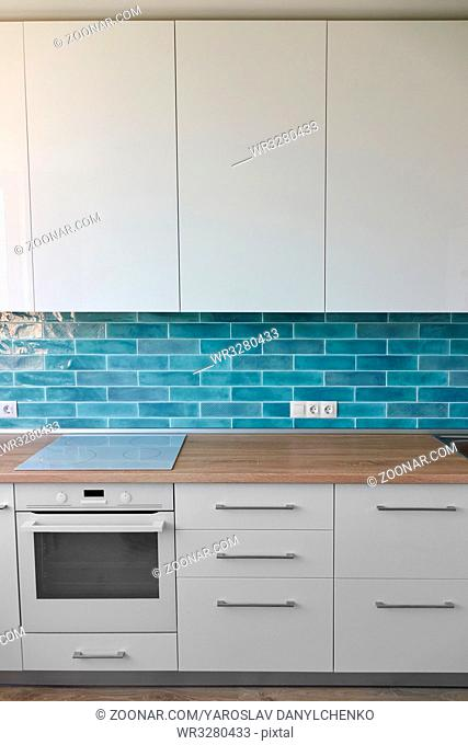 Part of the kitchen with hob, oven and brown top in white blue tones