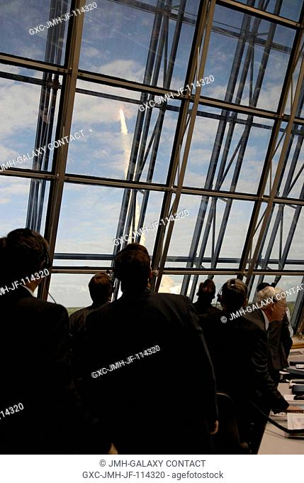Members of the space shuttle launch team watch Space Shuttle Atlantis' launch through the newly installed windows of Firing Room 4 in the Launch Control Center...