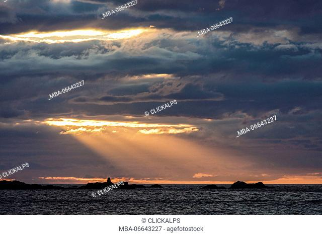 Rays of the midnight sun light up the lighthouse overlooking the sea Eggum Vestvagøy Lofoten Islands Norway Europe