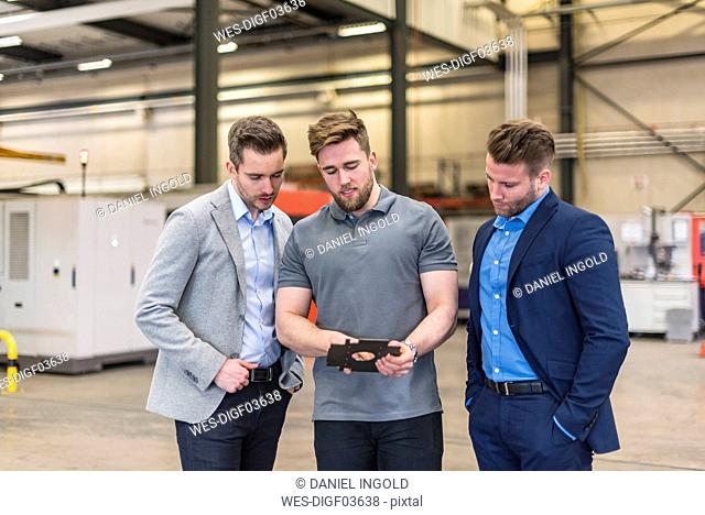 Employee explaining workpiece to businessmen on factory shop floor