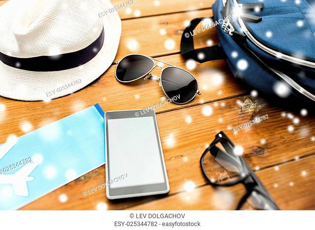 travel, tourism, technology and winter holidays concept - smartphone, airplane ticket and traveler personal stuff over snow