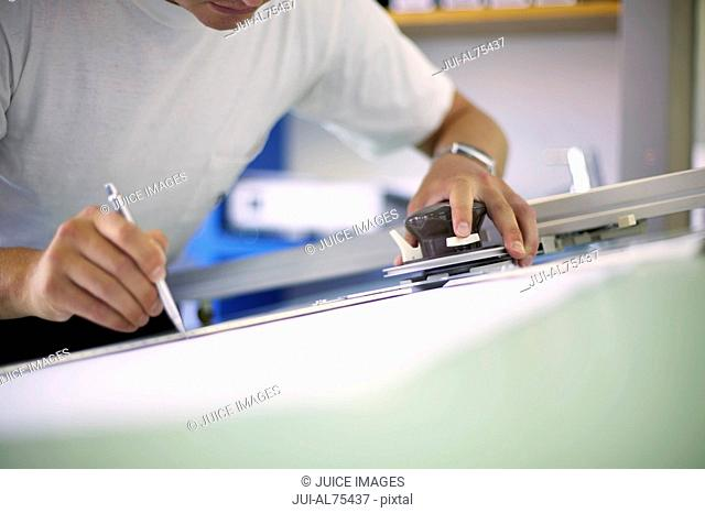 Detail view of man working on a drafting table
