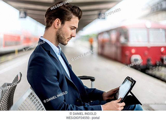 Businessman at the station using tablet