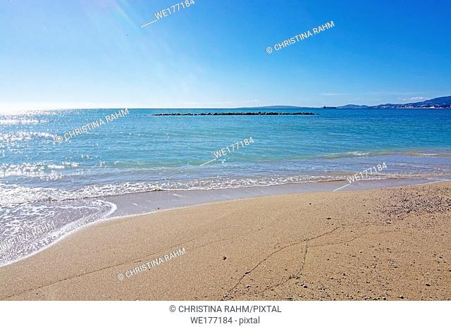 Untouched sand beach with wave residue pattern and blue sea in Mallorca, Spain