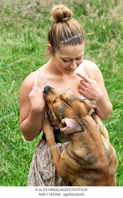 Young woman playing with pet dog