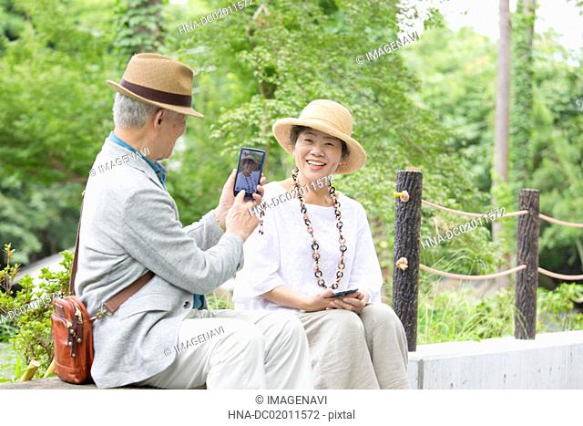 Senior couple taking photos with smart phone