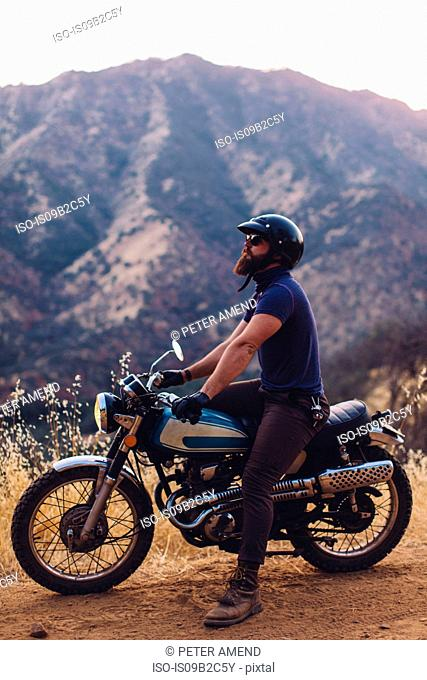 Man sitting on motorbike, looking at view, Sequoia National Park, California, USA