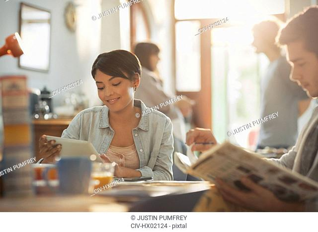 Young man and woman college students studying with book and digital tablet at table
