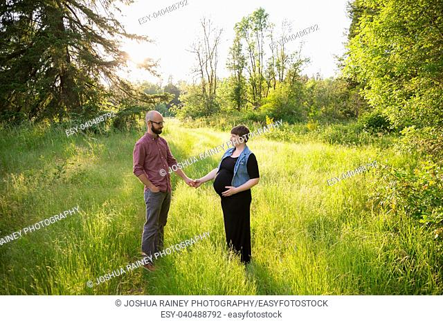 Man and a pregnant woman in a field in Oregon while the girl is in her third trimester. The couple is married and this husband and wife are expecting their...
