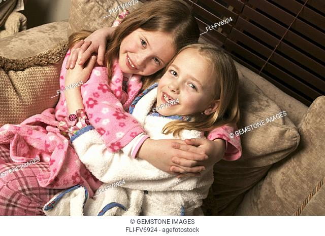 FV6924, Scott Dimond, Two Young Girls Hugging on Couch in Pajamas