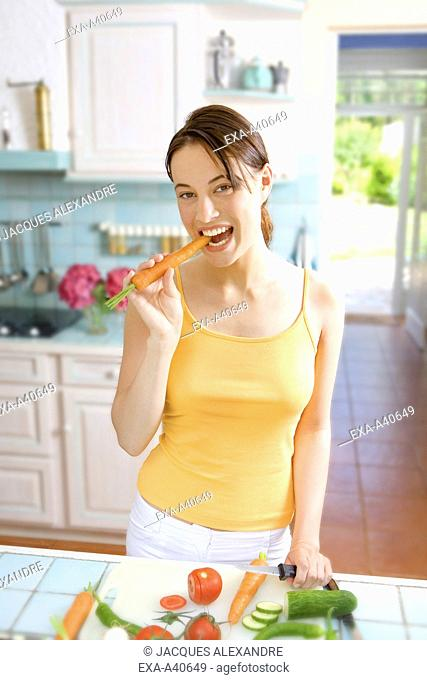 Young woman eating carrot in kitchen