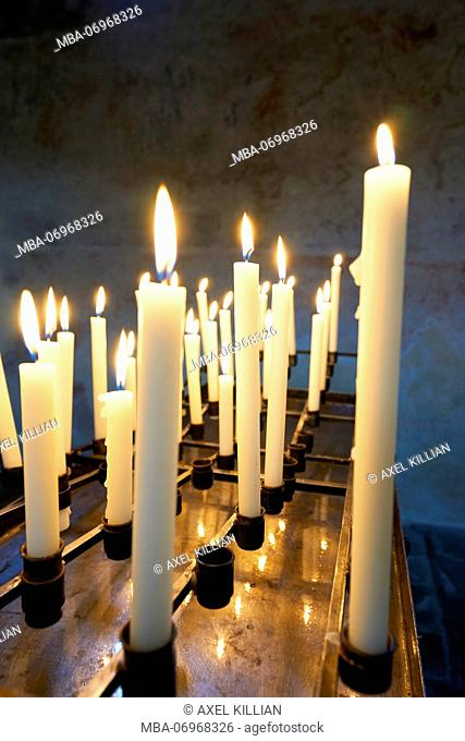 Many white candles are burning in a church, side by side, row, open space