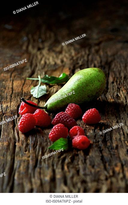 Pears and raspberries on old wooden surface