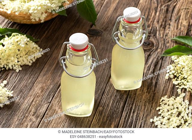 Two bottles of homemade elder flower syrup on a table