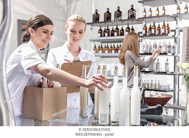 Two shop assistants in wellness shop packing bottles