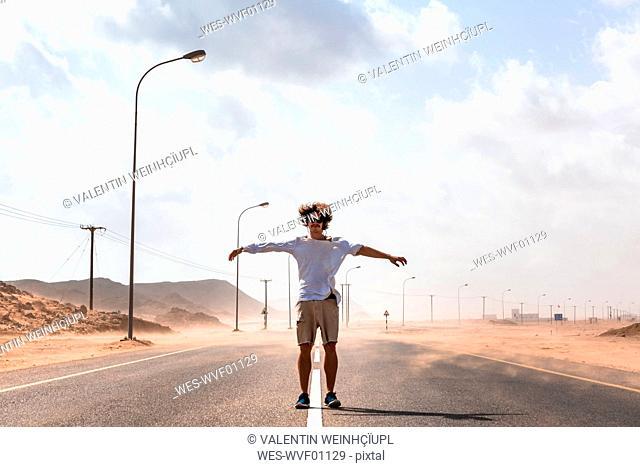 Sultanate Of Oman, Ras al Hadd, Desert road, Man standing in a sand storm