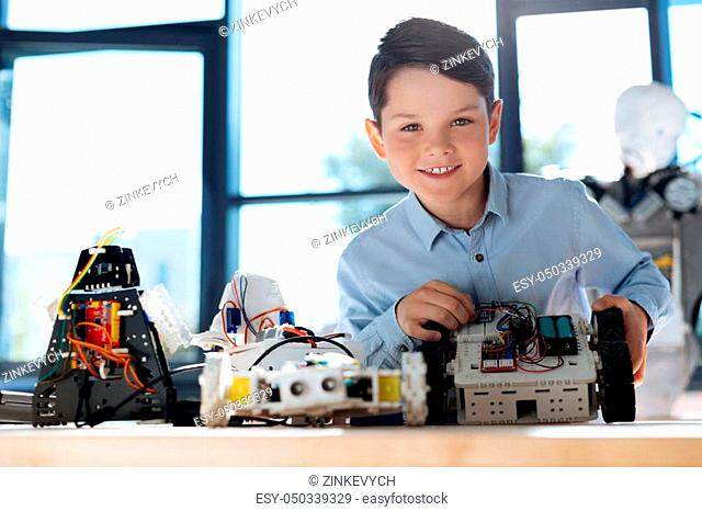 Fruit of creation. Cheerful pleasant boy sitting at the table with different robots on display and showing a robotic vehicle being the result of his work