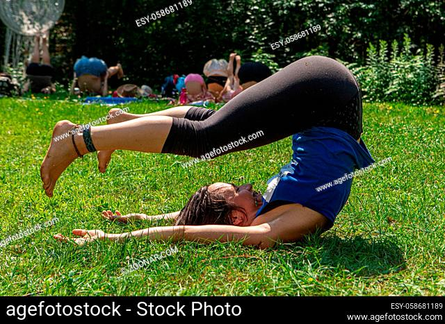 A close up view of a young caucasian woman practicing yoga, Diverse people enjoy outdoor yoga session in the background, during spiritual gathering