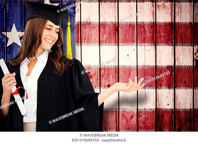 Composite image of a woman holding her hand out with a degree in her other hand as she smiles