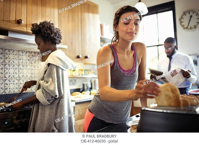 Woman toasting bread in toaster in kitchen