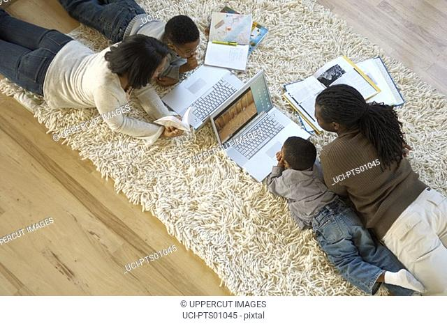 Family using laptops and doing homework on shag rug