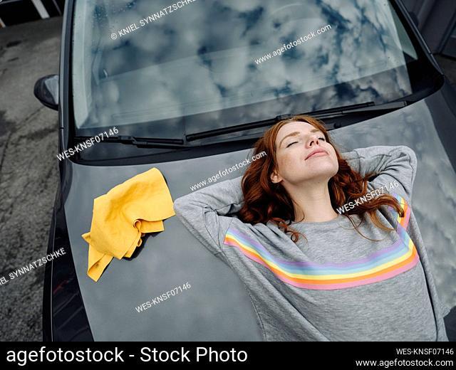 Redheaded woman lying on car bonnet