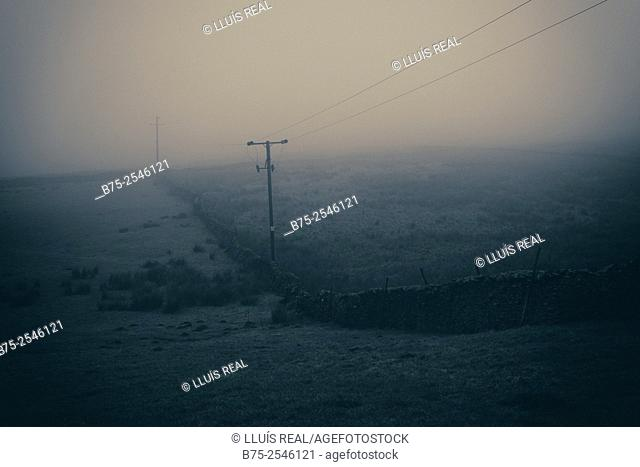 Rural landscape in a foggy day with a dry stone wall and electrical poles and wires. Yorkshire Dales, Skipton, England, UK, Europe