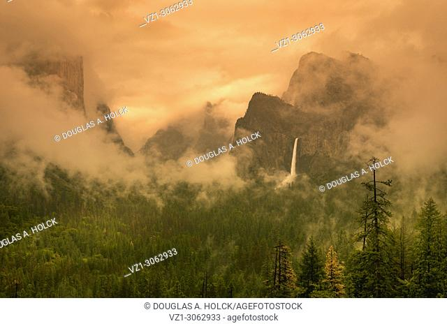 Sun and Clouds surround Yosemite's Bridalveil Fall during Spring Storm