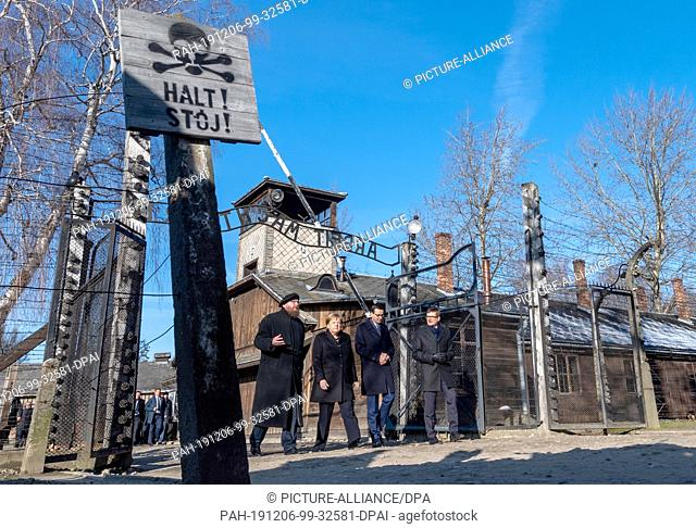 dpatop - 06 December 2019, Poland, Oswiecim: Federal Chancellor Angela Merkel (CDU) visits the former German Auschwitz concentration camp and walks under the...