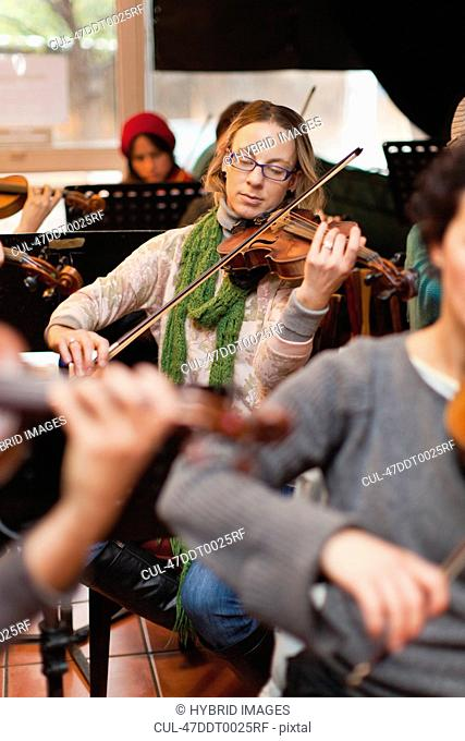 Violin player practicing with group