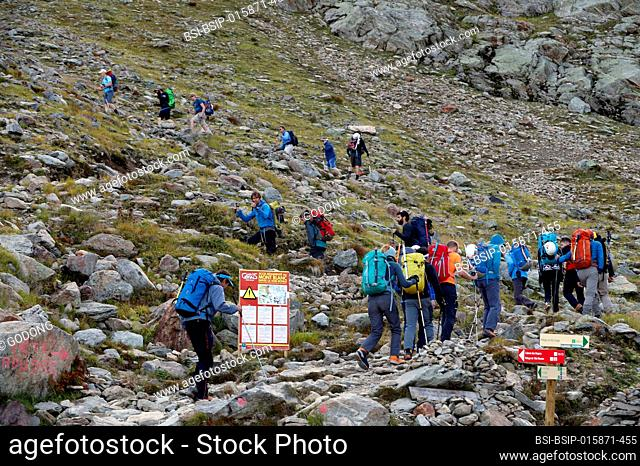 Alpinists during the ascent of Mont Blanc along the regular route via Gouter Refuge. Local Bye-Law. Regulated Access to Mont Blanc sign. France