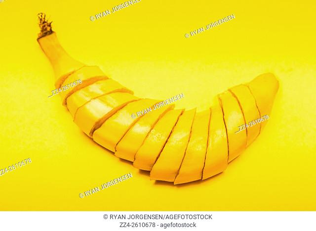 Banana tampered with and sliced up in mummy like dissections on yellow background. GMO frankenfruit