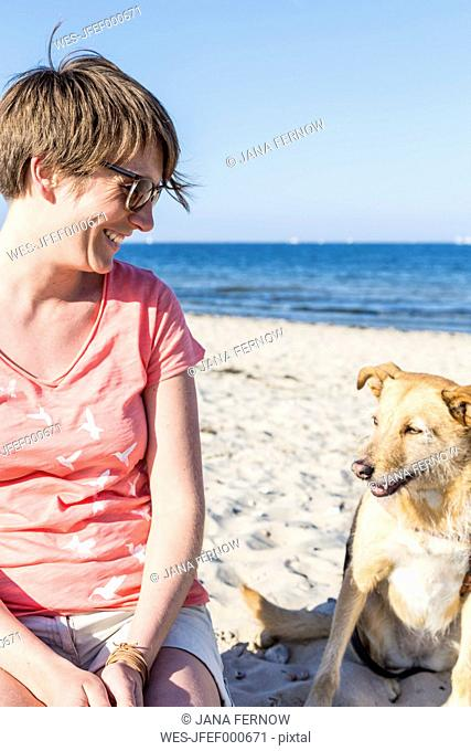 Germany, Kiel, smiling woman sitting with her dog on sandy beach