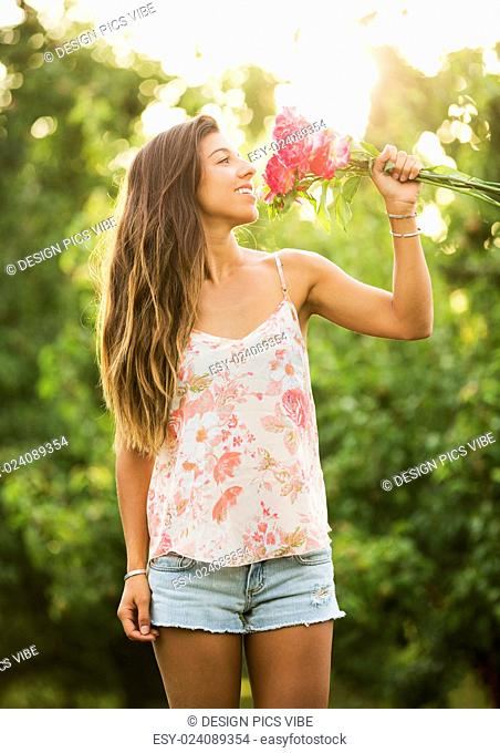 Beautiful Young Woman Smelling Flowers in Countryside, Summer Lifestyle