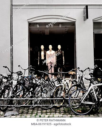 Bicycles on storefront with mannequins