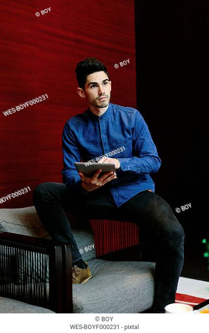Young businessman sitting on armchair of a lobby with his digital tablet watching something