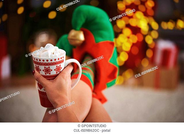 Woman wearing elf slippers holding hot chocolate