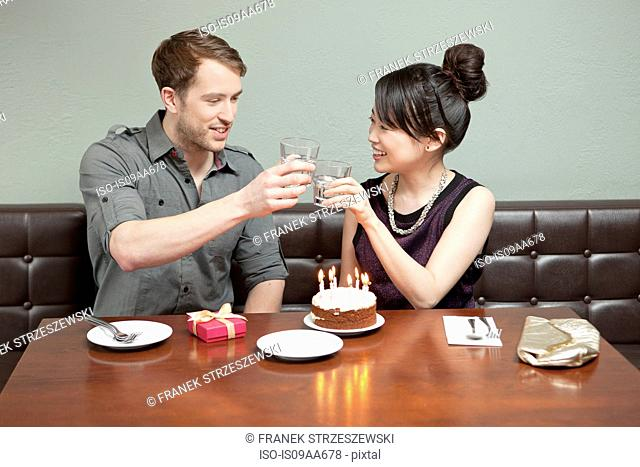 Young couple celebrating birthday in restaurant