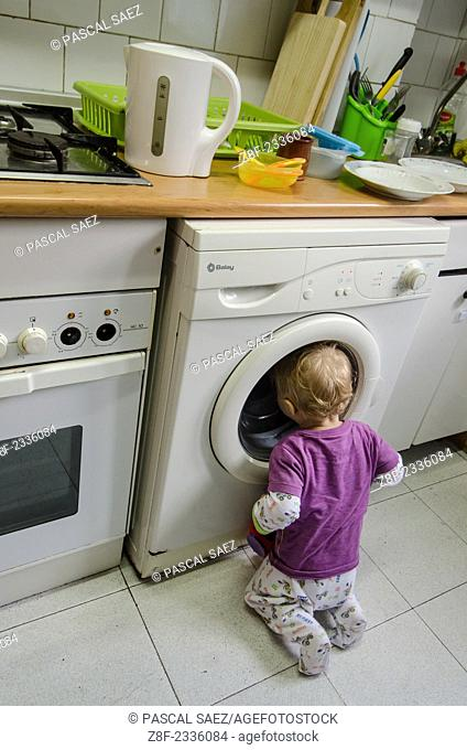 A baby boy (ca. 18 months old) watches laundry being washed in a washing machine