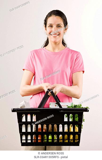 Woman carrying basket of groceries