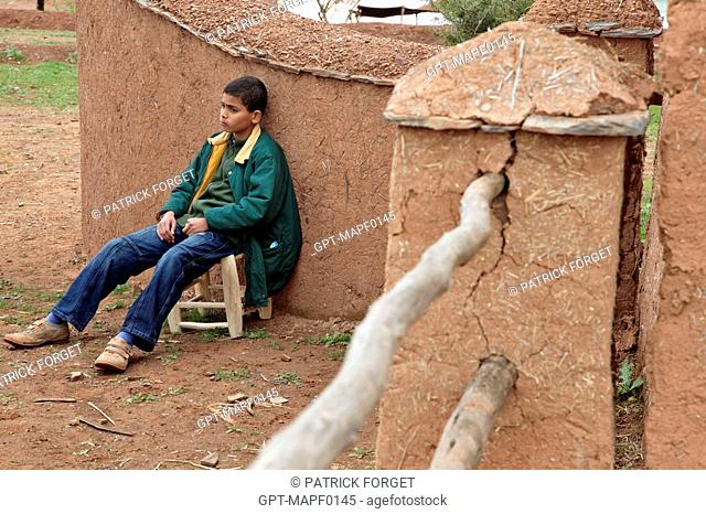 BERBER CHILD IN FRONT OF HIS HOUSE, TERRES D'AMANAR, TAHANAOUTE, AL HAOUZ, MOROCCO