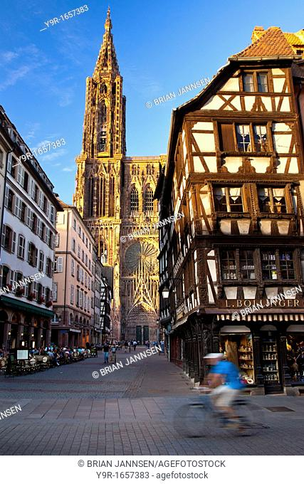 Bicycler rides past the massive Cathedral Notre Dame in Strasbourg, Bas Rhin Alsace France