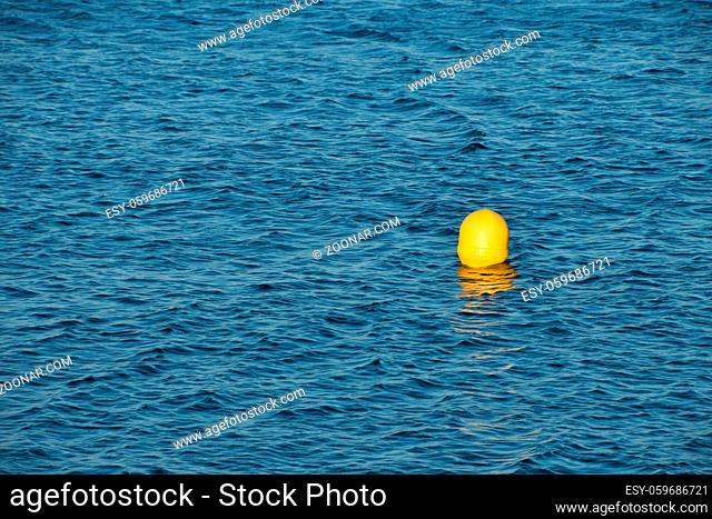 Turquoise blue sea water surface with ripples and waves, yellow floating buoy, high angle view