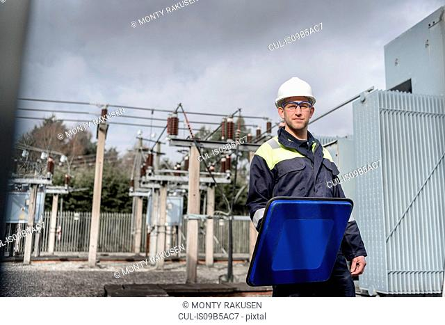 Worker using partial discharge detector in electricity substation