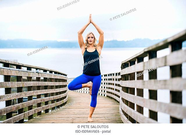 Portrait of young woman practicing standing tree yoga pose on wooden pier