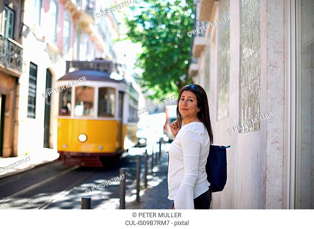 Woman in street, tram in background, Lisbon, Portugal