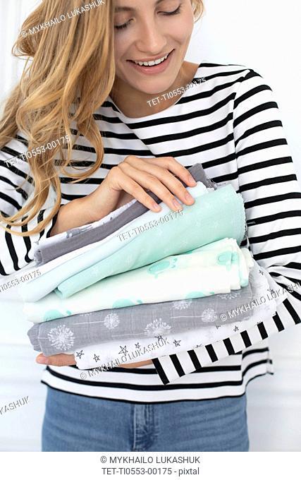 Woman holding stack of fabrics