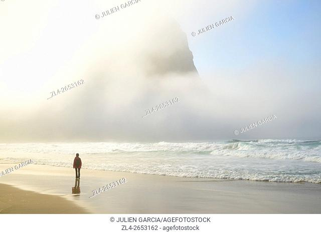 Norway, Nordland, Lofoten islands, Moskenesoy island, woman walking along the isolated beach of Kvalvika, sun breaking through the mist, Model Released