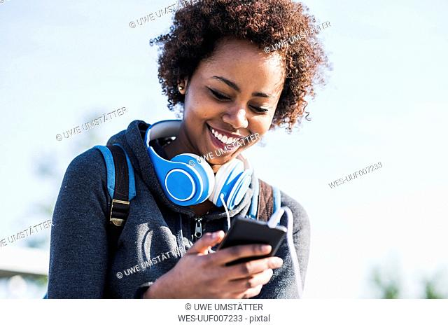 Smiling young woman wearing headphones looking at cell phone outdoors